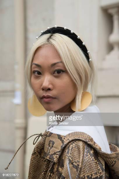 Fashion blogger Vanessa Hongof The Haute Pursuit wears a Valentino coat, Paula Mendoza earrings and Altuzarra headband day 6 of Paris Womens Fashion...