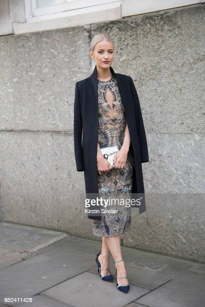 Fashion blogger Victoria McGrath wears a Julien MacDonald dress All Saints coat Malone Souliers shoes and Bvlgari bag on day 2 of London Womens...