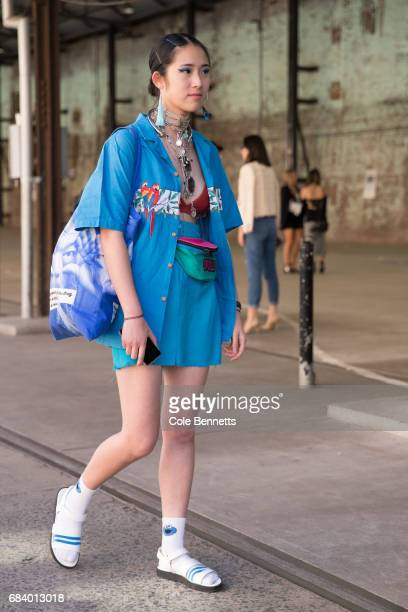 A fashion blogger wearing a blue rosella button up shirt undone with blue skirt and socks with sandles during MercedesBenz Fashion Week Resort 18...