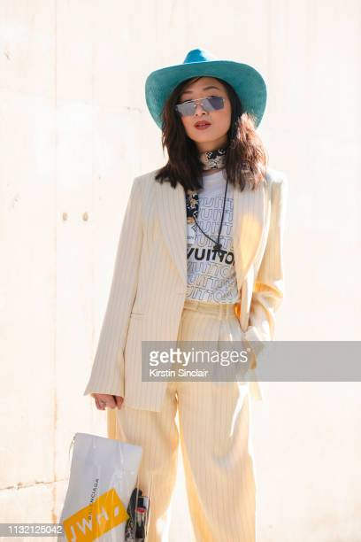 Fashion blogger Wenwen Stokes wears a Louis Vuitton T shirt and scarf Topshop suit Miu Miu sunglasses Dover Street Market hat and a Balenciaga bag...