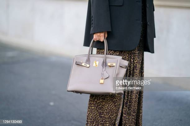 Fashion blogger Xiayan wears a black oversized blazer jacket from Les Coyotes de Paris, a brown gathered leopard print long dress from Les Coyotes de...