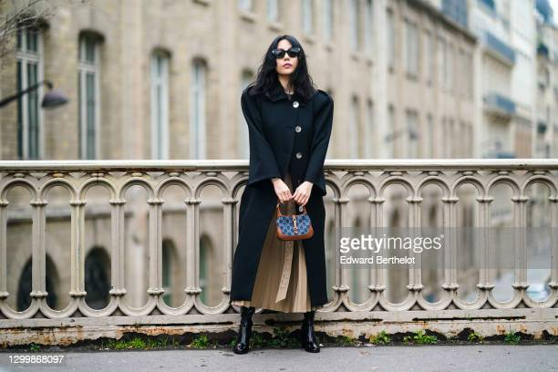 Fashion blogger Xiayan wears sunglasses from Bottega Veneta, a black wool long coat with shoulder pads from Lovechild, a gray tank top from...