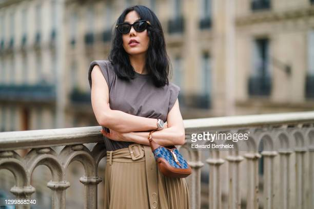 Fashion blogger Xiayan wears sunglasses from Bottega Veneta, a gray tank top from Copenhagen Muse, a beige pleated long skirt from Copenhagen Muse, a...