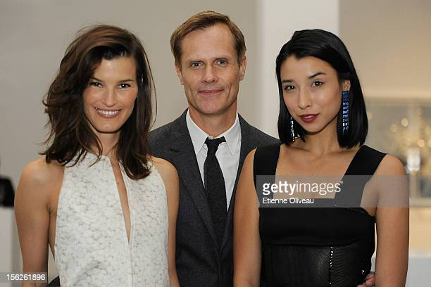 Fashion bloggers Hanneli Mustaparta and Lily Kwong pose for pictures with a guest during the Calvin Klein special dinner at the Long March Space in...