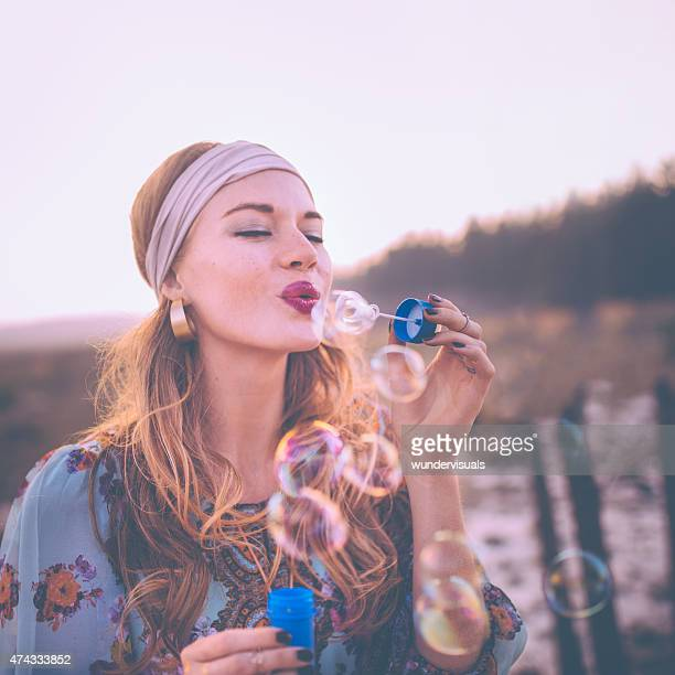 Fashion Boho girl blowing bubbles in nature