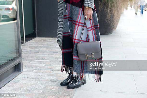 Fashion Buyer and Owner of Kabuki Paris Elina Hallimi wears an Acne cape Barbara Bui trousers Hermes bag and Givenchy shoes on day 3 during London...