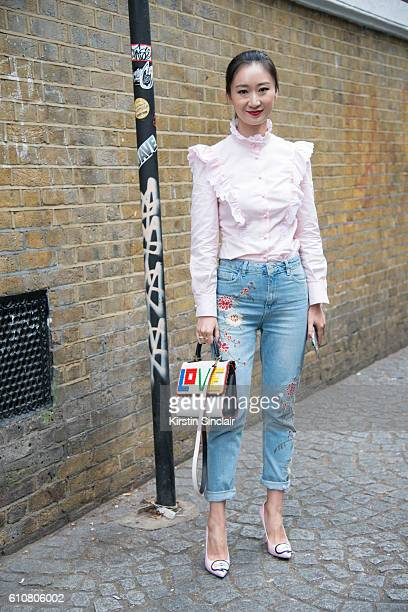 Fashion buyer Nicole Xu wears a Philosophy top Topshop jeans Les Petit Joueurs bag and Sophia Webster shoes on day 5 of London Womens Fashion Week...