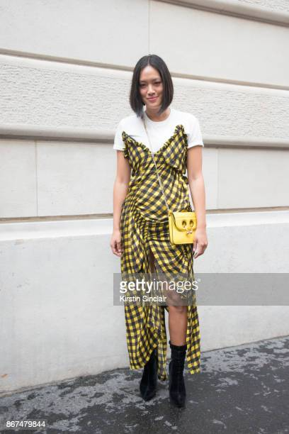 Fashion buying manager at mytheresacom Tiffany Hsu wears a Preen dress JW Anderson bag and Alexander Wang boots day 3 of Paris Womens Fashion Week...