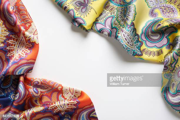 A fashion clothing image of some paisley patterned silk or satin scarves