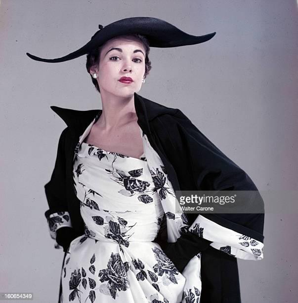 Fashion Collections Spring 1954. Un mannequin pose en studio pour présenter les collections de couture du printemps 1954, vêtue d'une robe à fleurs, d'un manteau noir et d'un chapeau noir à larges bords.