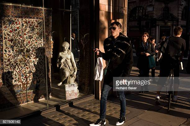 A fashion conscious male with a small girl statue credited to the 19th century Florenceborn artist Raffaello Romanelli In afternoon sunlight the...