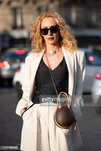 Fashion consultant Elina Halimi wears a Louis Vuitton bag Celine sunglasses Alexander Arutyunov suit on February 27 2019 in Paris France