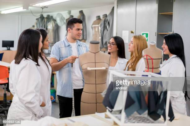 Fashion design students in class listening to their teacher