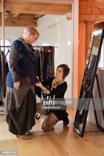 """fashion designer adjusting clothing on plus size woman. - """"martine doucet"""" or martinedoucet stock pictures, royalty-free photos & images"""