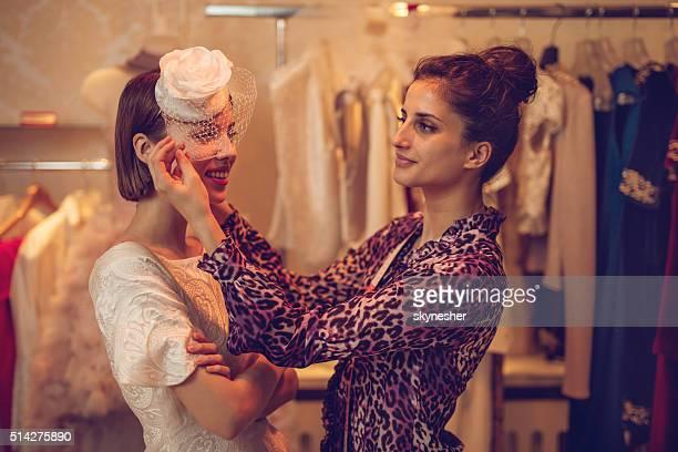Fashion designer adjusting lace on bride's hat in design studio.