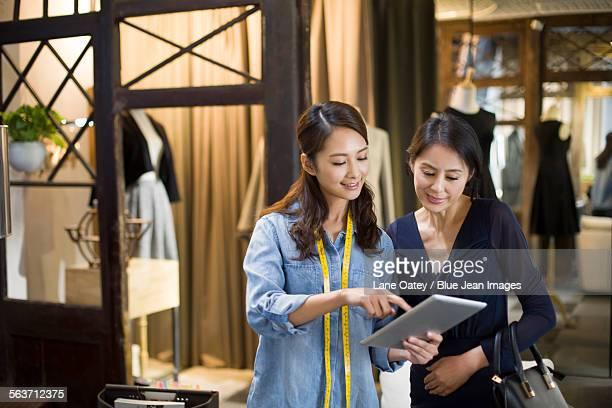 Fashion designer and customer looking at digital tablet