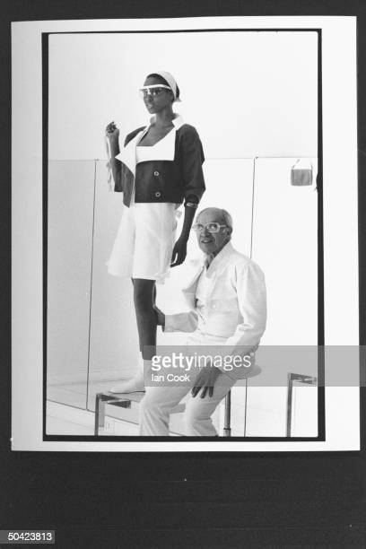 Fashion designer Andre Courreges posing w black model as she poses in white shorts w flamboyant short jacket accented w famous white lowtop boots in...
