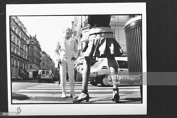 Fashion designer Andre Courreges who created the first miniskirt fashions 25 yrs ago admiring model wearing one of his latest miniskirt creations on...