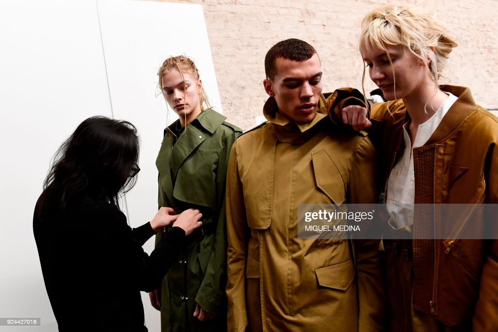 TOPSHOT - Fashion designer Atsushi Nakashima (L) prepares models backstage prior to the women's Fall/Winter 2018/2019 collection fashion show by Atsushi Nakashima, in Milan, on February 26, 2018. / AFP PHOTO / Miguel MEDINA
