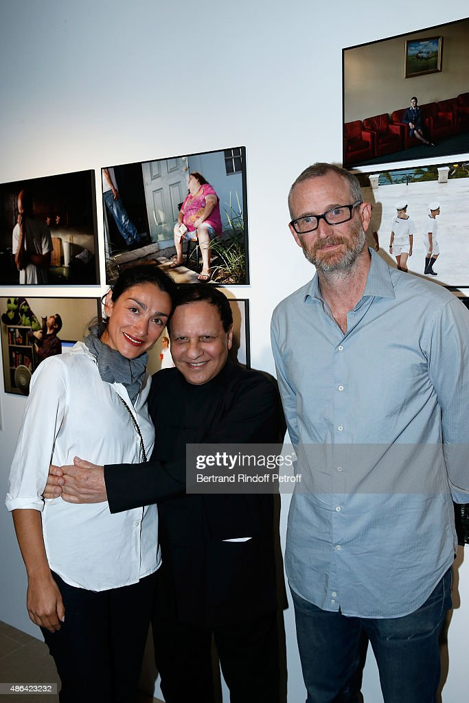 Fashion Designer Azzedine Alaia standing between Contemporary Artist Mike Bouchet and his companion Galerist Parisa Kind attend the 'World Press Photo 2015' Exhibition Opening Party, held at Galerie Azzedine Alaïa on September 3, 2015 in Paris, France.
