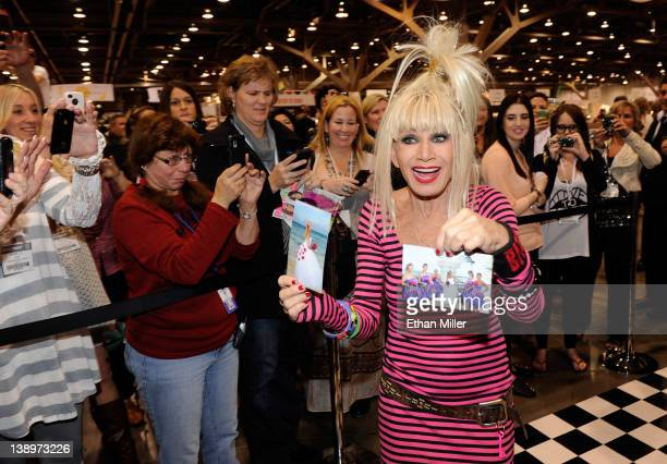 Fashion designer Betsey Johnson shows off pictures she was handed of people wearing her designs as she appears at the MAGIC clothing industry...