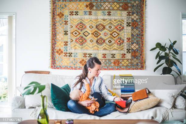 fashion designer breastfeeding daughter while looking at fabric swatch on sofa in living room - adult breastfeeding stock pictures, royalty-free photos & images