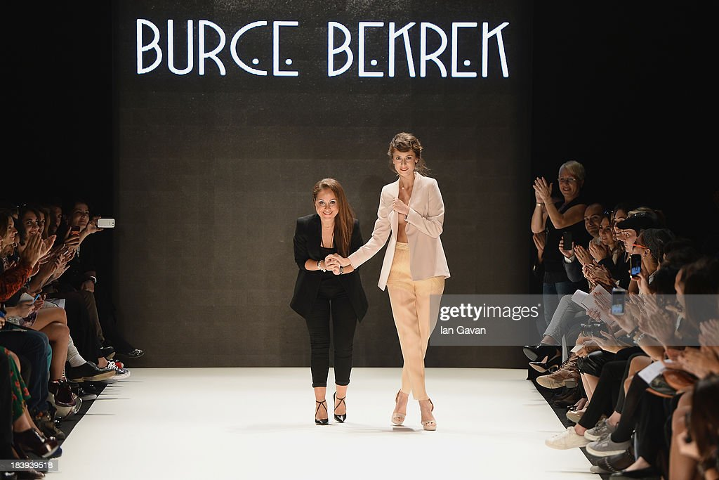 Fashion designer Burce Bekrek (L) and a model walk the runway at the Burce Bekrek show during Mercedes-Benz Fashion Week Istanbul s/s 2014 Presented By American Express on October 10, 2013 in Istanbul, Turkey.