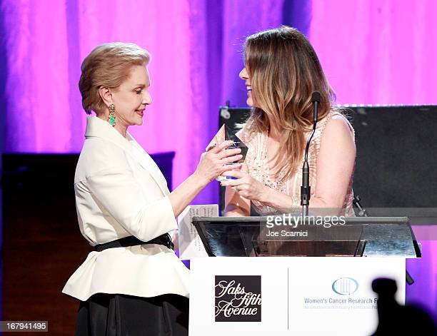 Fashion designer Carolina Herrera accepts the Nat King Cole Award from EIF Women's Cancer Research Fund honorary chair Rita Wilson onstage during EIF...