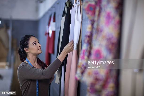 Fashion designer checking dresses in factory