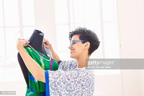 fashion designer choosing jewelery with dress.