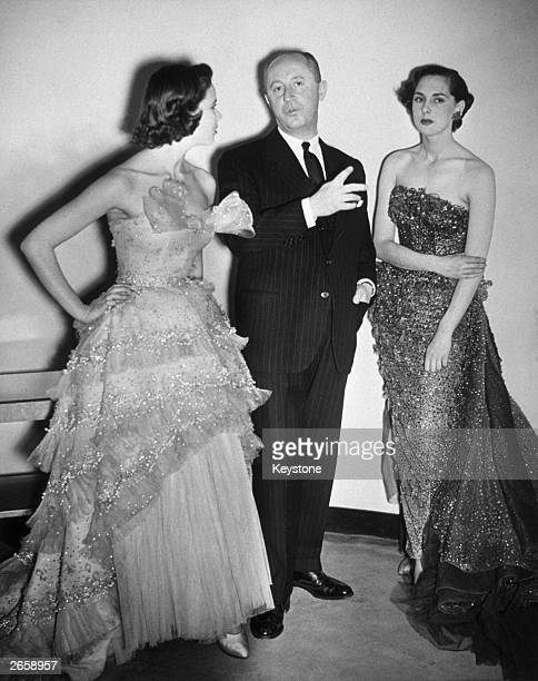 Fashion designer Christian Dior with two models wearing his creations