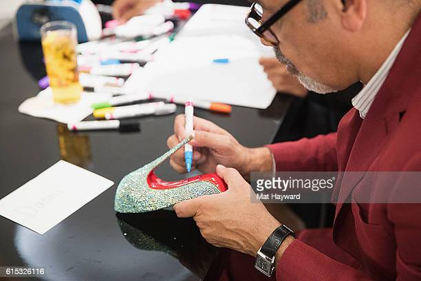 Fashion designer Christian Louboutin paints an autograph during a personal appearance at Nordstrom Downton Seattle on October 17 2016 in Seattle...