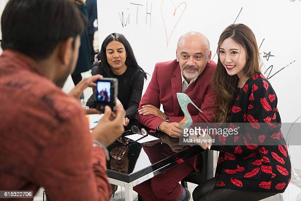 Fashion designer Christian Louboutin poses for a photo with a customer during a personal appearance at Nordstrom Downton Seattle on October 17 2016...