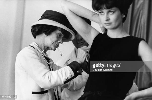 Fashion designer Coco Chanel adjusts the armhole of a model's dress with an assistant