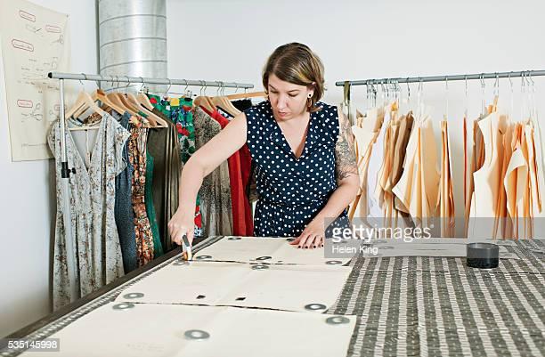 fashion designer cutting out garment pieces - top garment stock-fotos und bilder