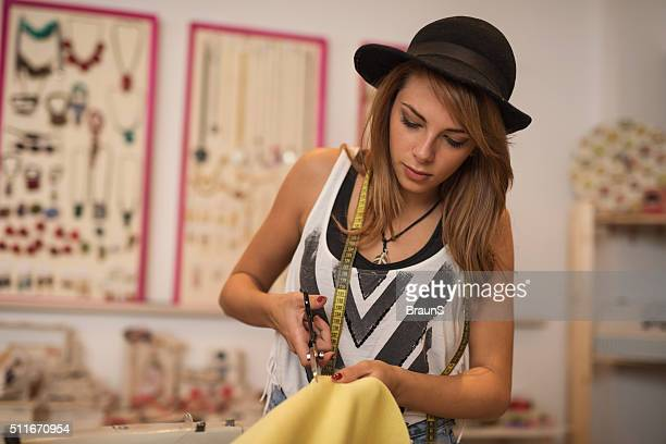Fashion designer cutting yellow material in a clothing design studio.