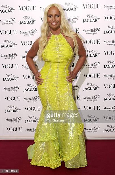 Fashion designer Donatella Versace in bright yellow evening dress with hands on hips at celebrity fashion show at Waddesdon Manor