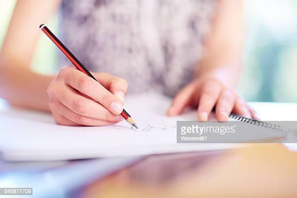 Fashion designer drawing on paper