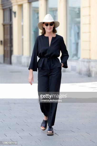 Fashion designer Eva Lutz, wearing a black blouse by Ganni and matching black pants by Ganni, a white hat by Horisaki Design, black platform sandals...