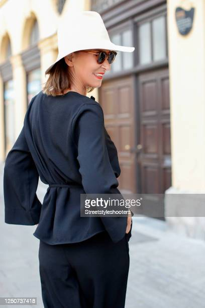 Fashion designer Eva Lutz, wearing a black blouse by Ganni and matching black pants by Ganni, a white hat by Horisaki Design and sunglasses by...