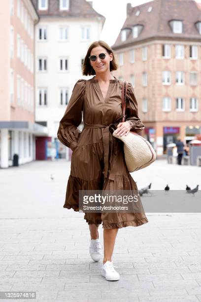 Fashion designer Eva Lutz wearing a long brown split neck tie-waist dress with long puff sleeves, ruffled and gathered details by Ulla Johnson, white...