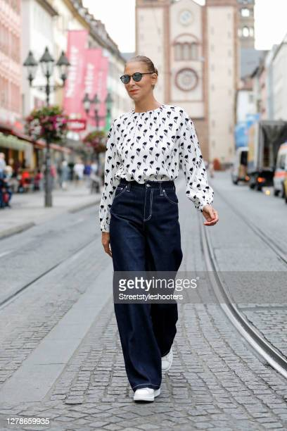 Fashion designer Eva Lutz wearing a white blouse with black flower print by Odeeh, dark blue high waisted and wide leg denim jeans by Chloe, white...