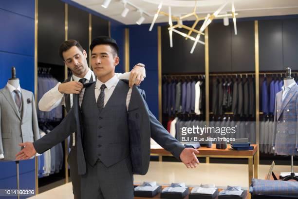 fashion designer examining suit on customer - メンズウェア ストックフォトと画像
