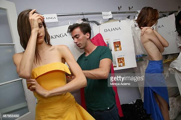 Fashion designer Fernando Garcia prepares a model backstage before the Monse fashion show during Spring 2016 MADE Fashion Week at Norwood Club on...