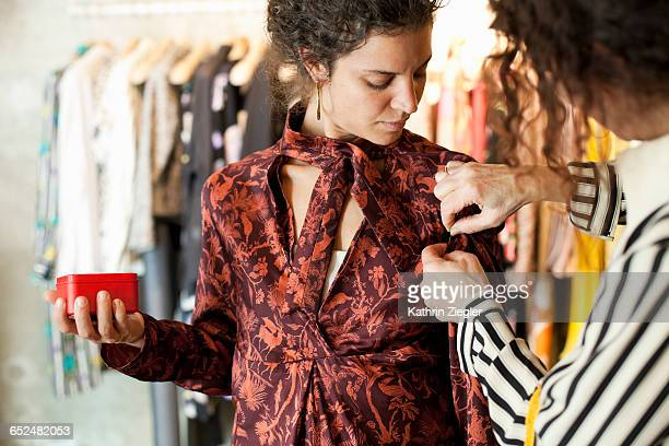 fashion designer fitting dress on young woman