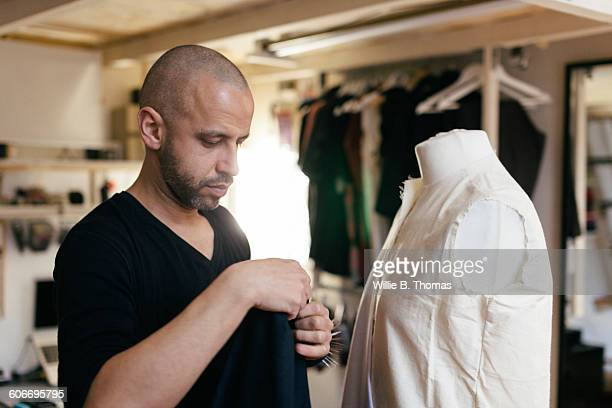 Fashion Designer fitting garment to Mannequin