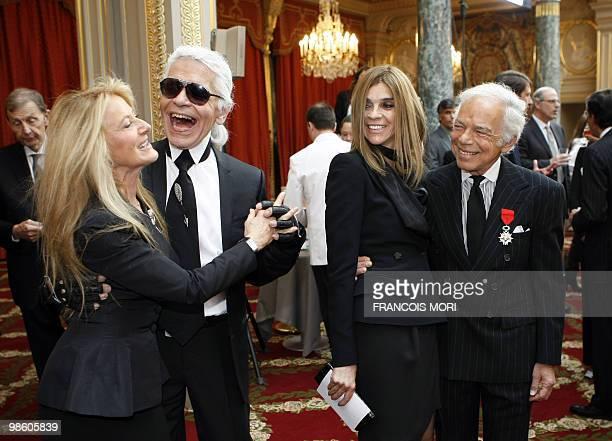 US fashion designer flanked by chief editor of the French edition of Vogue Carine Roitfeld looks at German fashion designer Karl Lagerfeld dancing...