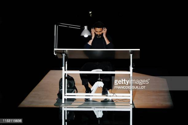 Fashion designer for Schiaparelli Daniel Roseberry sits behind a desk on the catwalk during the Women's FallWinter 2019/2020 Haute Couture collection...