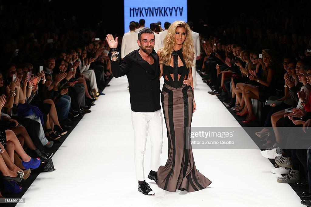 Fashion designer Hakan Akkaya (L) and model Cagla Sikel (R) walk the runway at the Hakan Akkaya show during Mercedes-Benz Fashion Week Istanbul s/s 2014 presented by American Express on October 9, 2013 in Istanbul, Turkey.