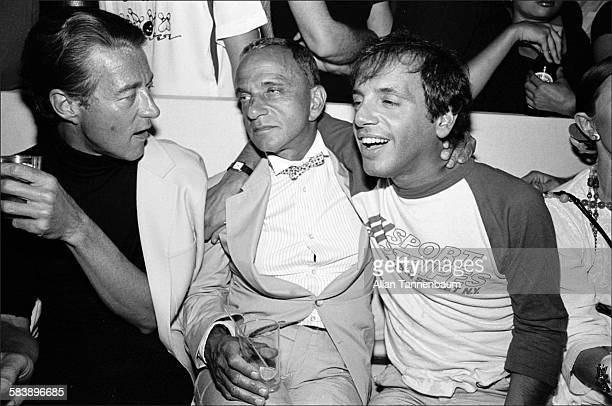 Fashion designer Halston attorney Roy Cohn and nightclub owner Steve Rubell sit together during Victor Hugo's performance at the Mudd Club New York...